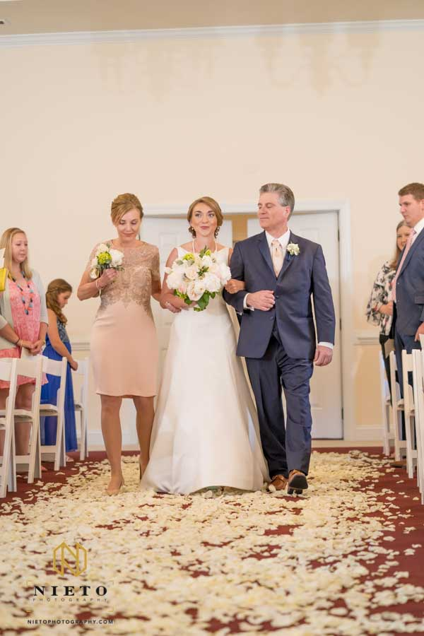 birde smiling as her mother and father escort her down the aisle