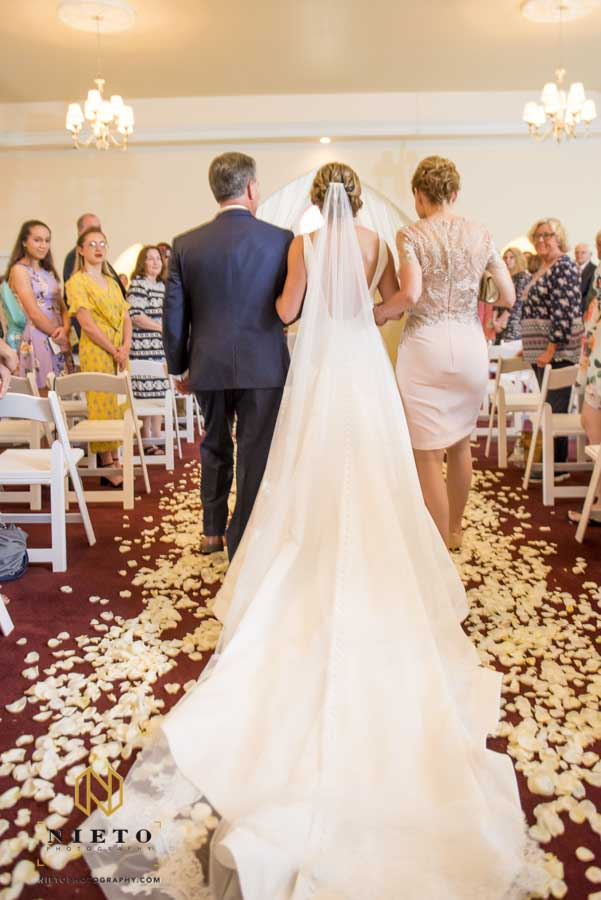 brides veil trailing behind her as her mother and father escort her down the aisle in the Hudson Manor Chapel