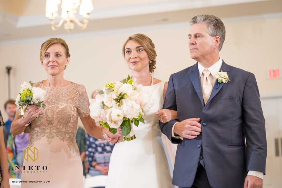 bride being escorted by both her mother and father down the aisle