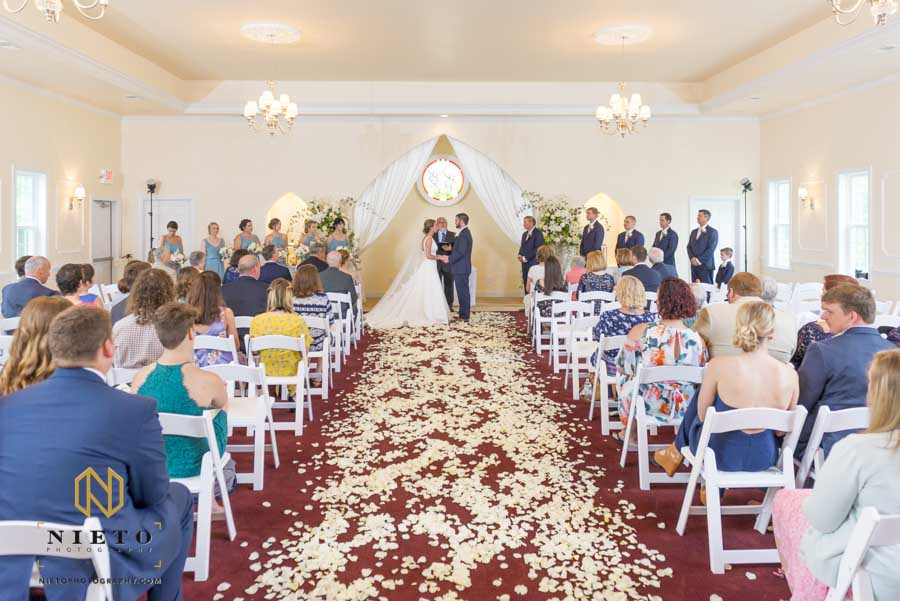 wide shot of the hudson manor chapel wedding with petals on the floor and guest in the chairs
