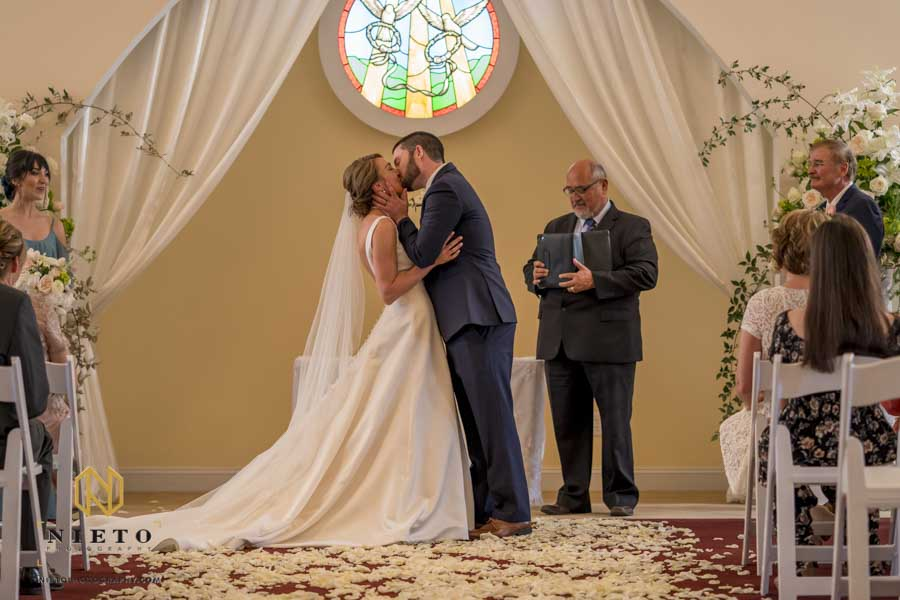 bride and grooms first kiss at their Hudson Manor chapel wedding