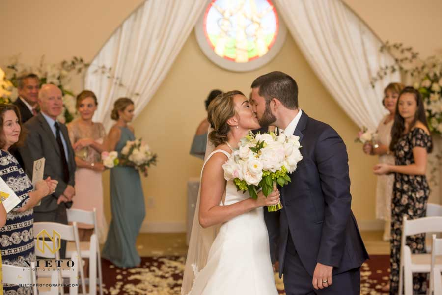 bride and groom kissing as they are walking down the aisle at their Hudson Manor chapel wedding