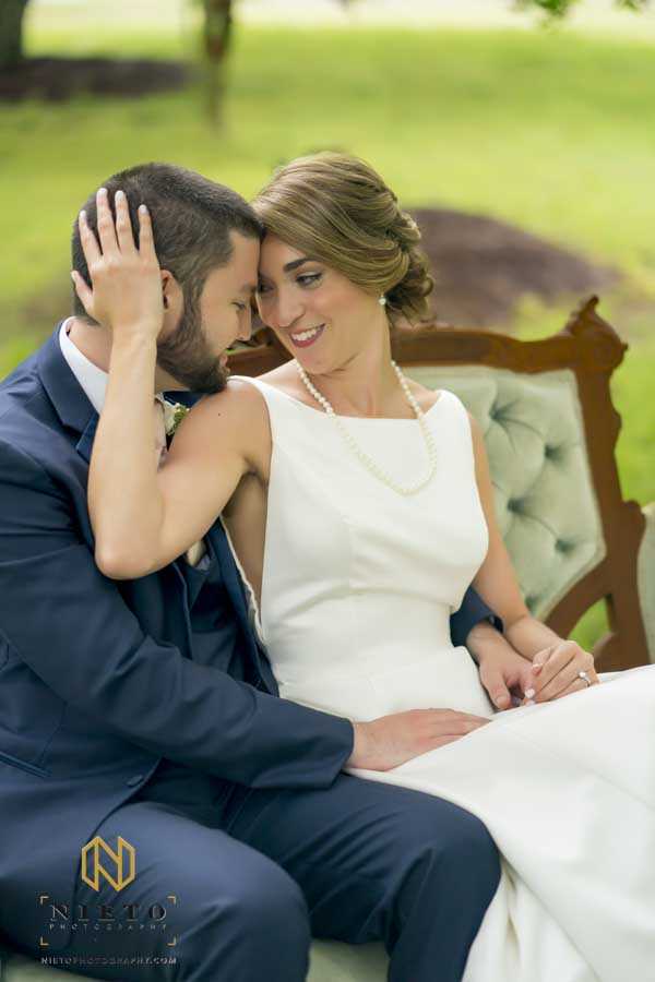 bride holding the head of the groom as they sit together
