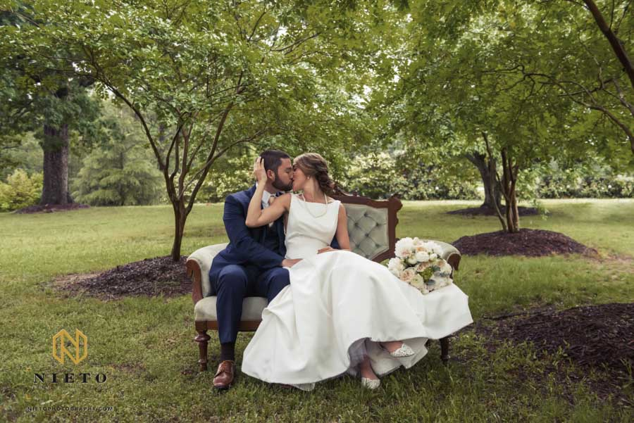 groom and bride kissing in a Homemade-Bride chair at the Hudson Manor