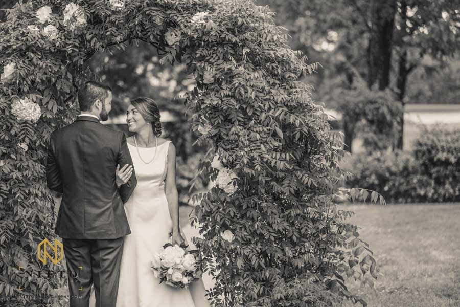 black and white image of the bride looking at the groom smiling at him