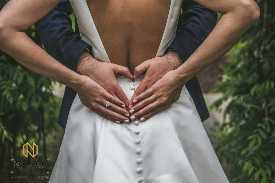 closeup of the groom and brides hands together making a heart