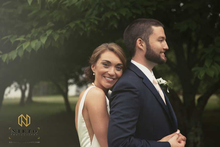 bride smiling at the camera as she hugs the groom from behind
