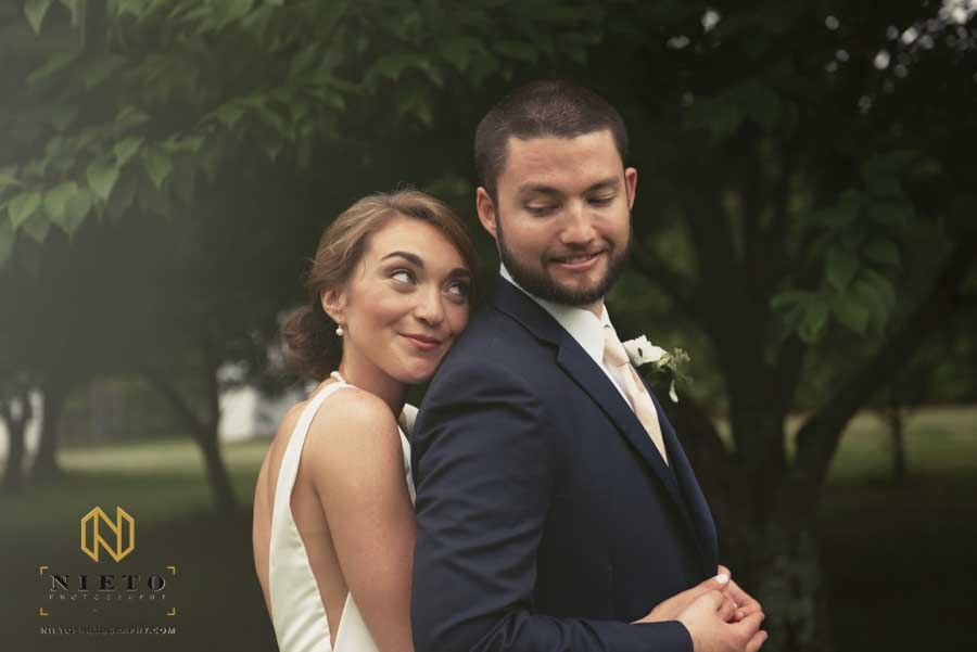 bride looking over the grooms shoulder as she hugs him from behind