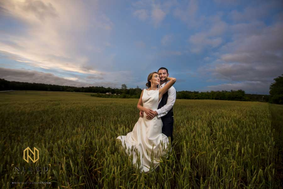 bride reaching back from to kiss the groom while they stand in a field under blue skies at the Hudson Manor