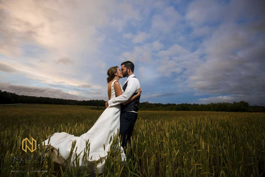 Bride and groom kissing in a hay field with a blue sky behind them