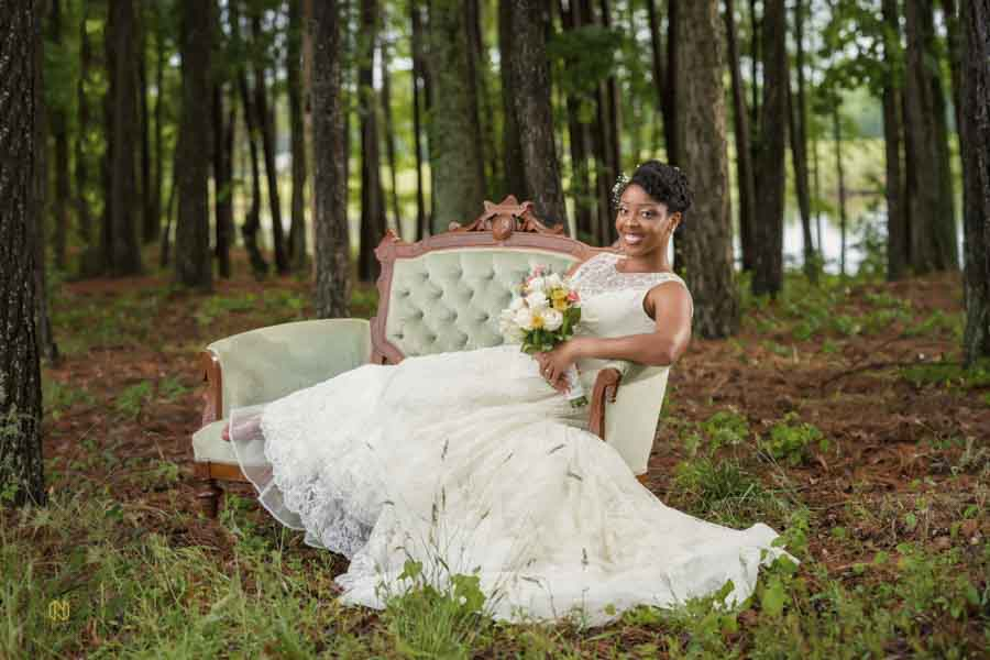 bride smiling at camera during her portrait session while sitting in a green chair
