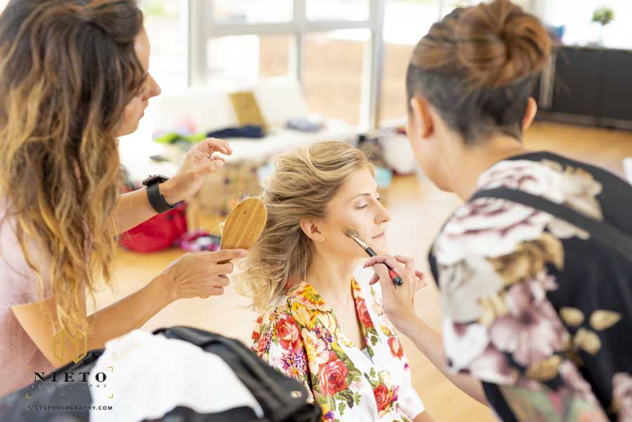 bride having her hair and makeup done at the same time