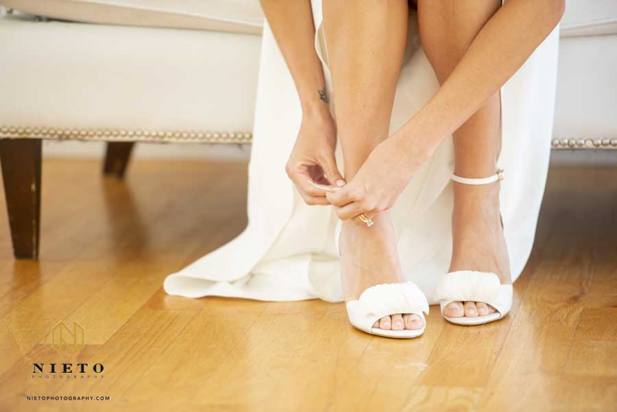 closeup of bride putting on her wedding shoes