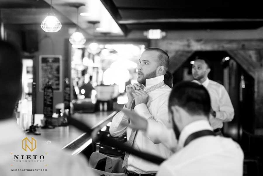 black and white image of the groom adjusting her tie at Isaac Hunters Tavern