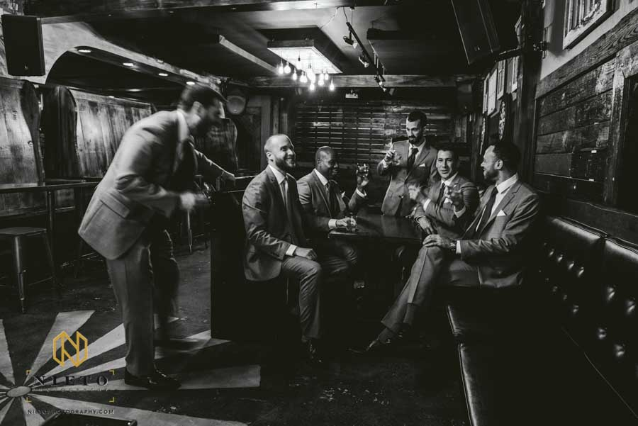 black and white image of groomsmen drinking around a table at Isaac Hunters Tavern in downtown Raleigh