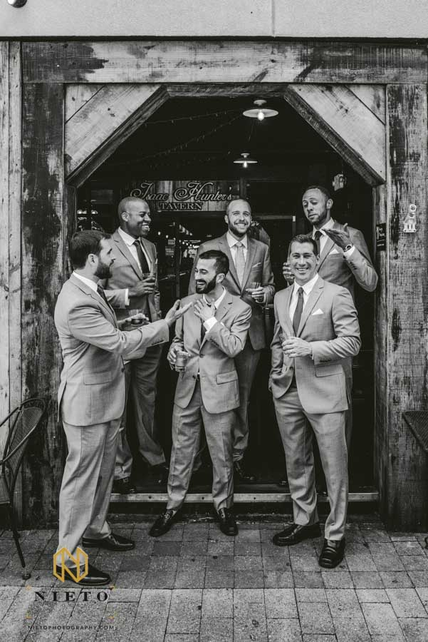 Black and white image of the groom and his groomsmen talking and laughing outside of Isaac Hunters Tavern