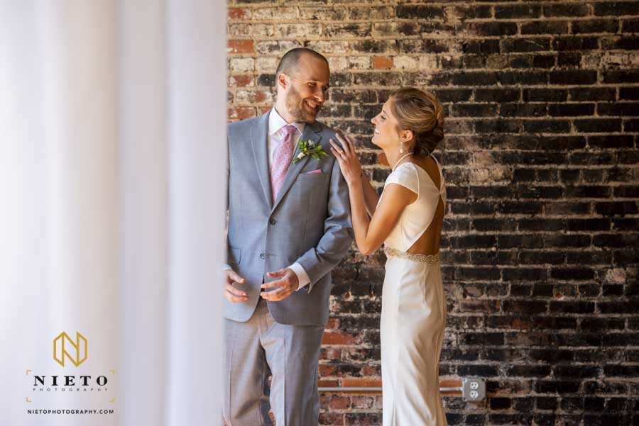 the groom smiling as he sees his bride for the first time during their Stockroom first look