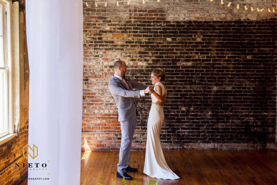 bride and groom dancing together during their first look at their stockroom wedding