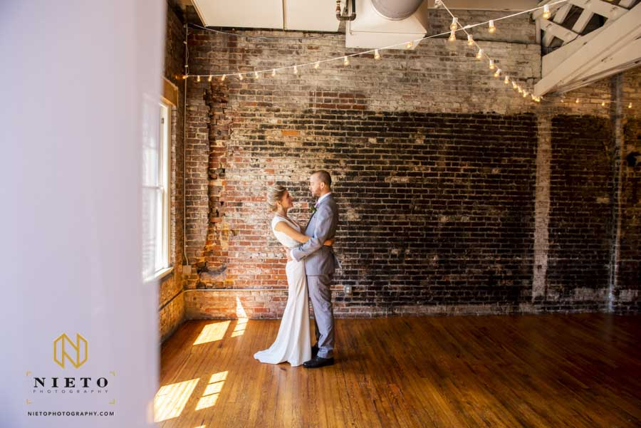 bride and groom hugging in front of a window at the Stockroom
