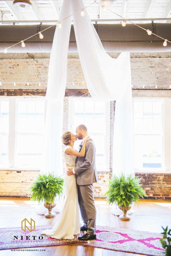 bride and groom kissing during their first look at the ceremony site of their Stockroom Wedding