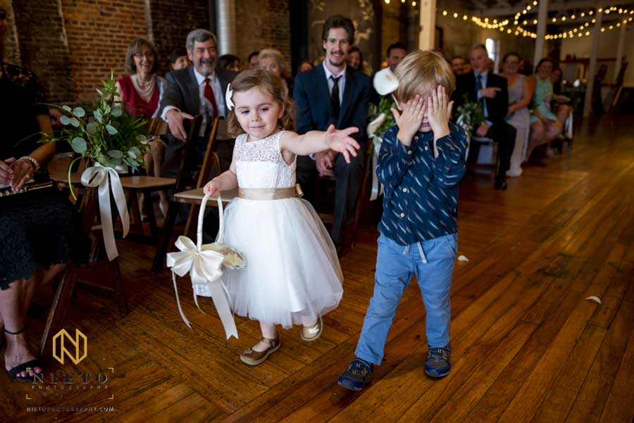 flower girl throwing petals while walking down the aisle at the stockroom wedding ceremony