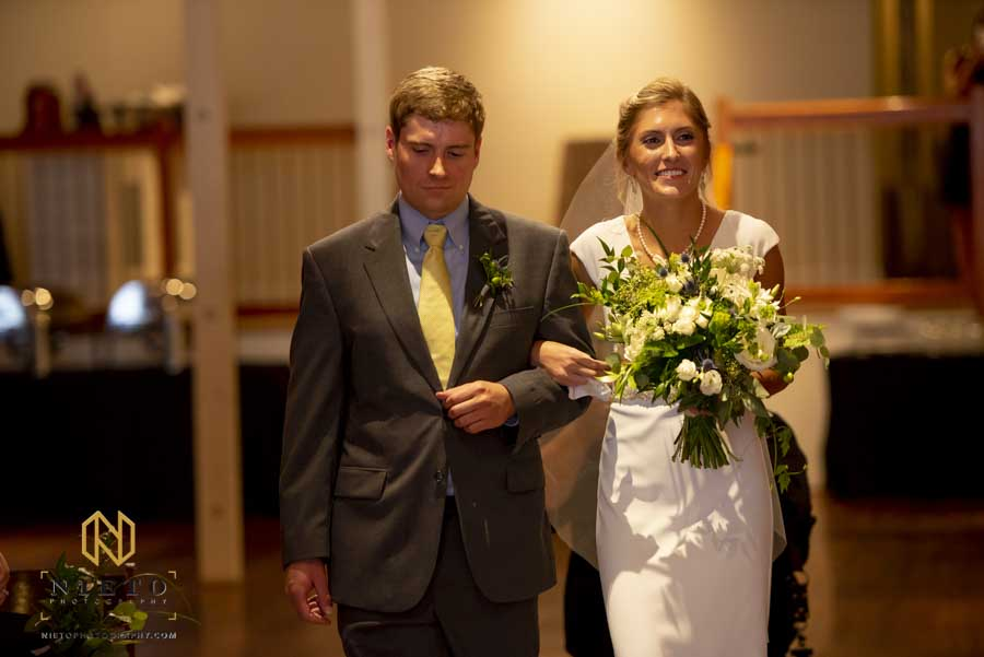 bride being escorted by her brother during a stockroom wedding