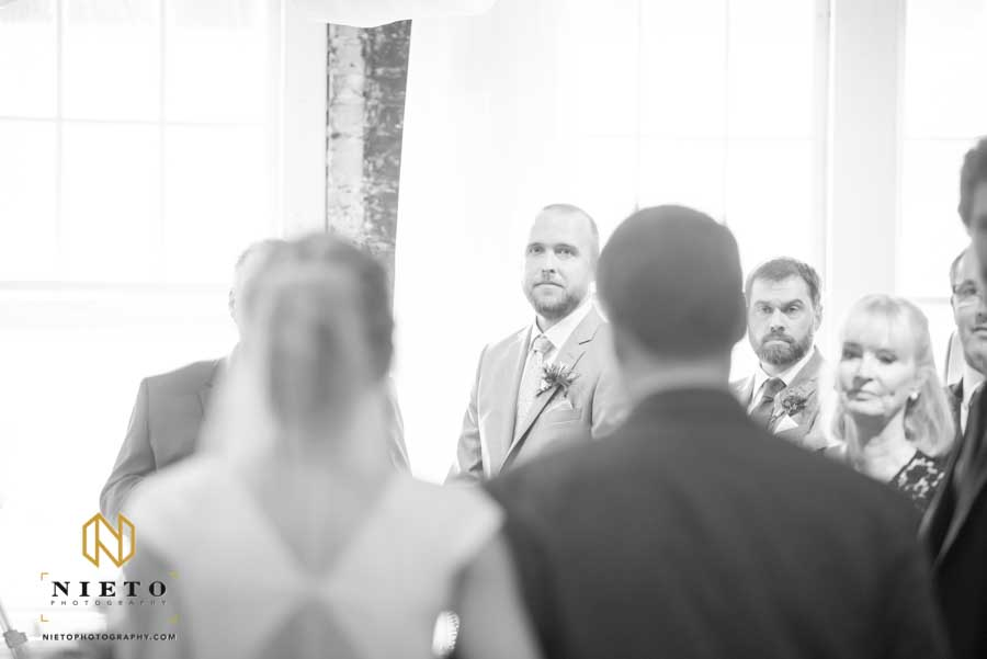 black and white image of the groom looking at the bride as she walks down the aisle during their Stockroom wedding ceremony
