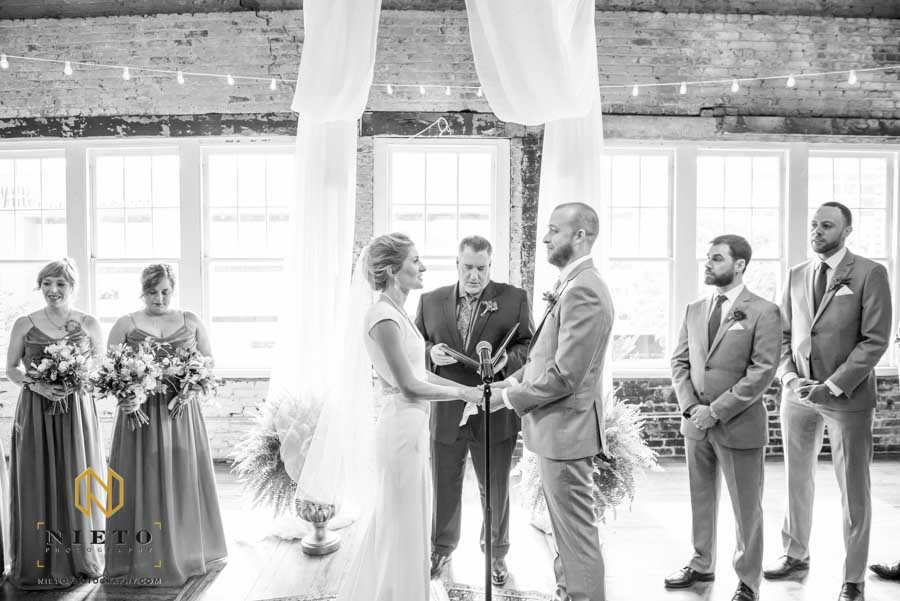 black and white image of the bride and groom holding hands during their Stockroom wedding ceremony