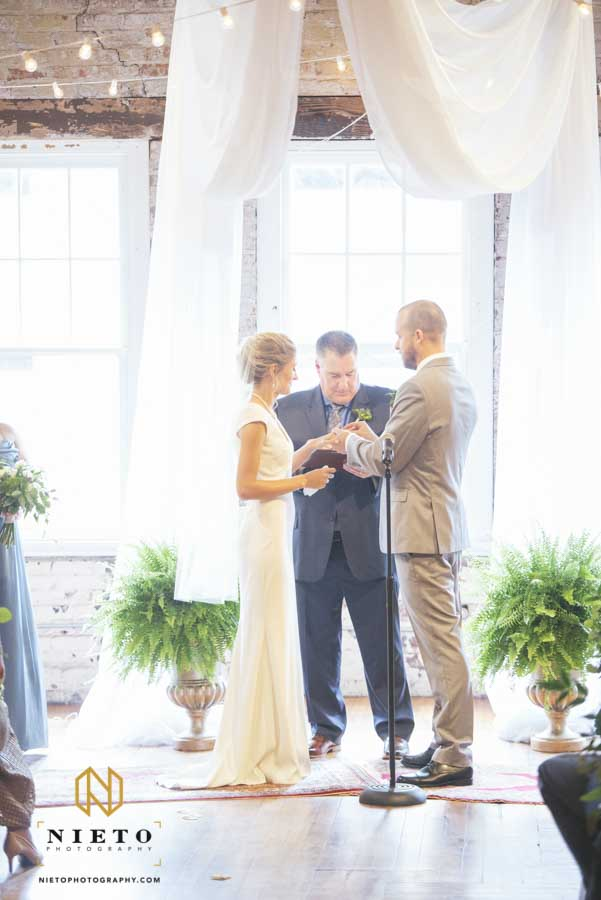 groom placing the ring on the brides hand