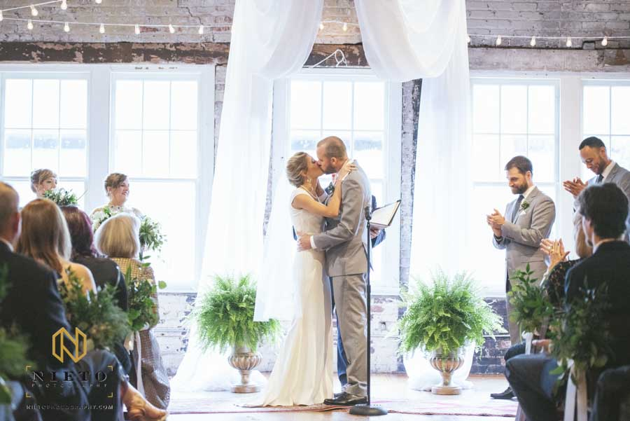 the bride and groom kissing for the first time during their stockroom wedding