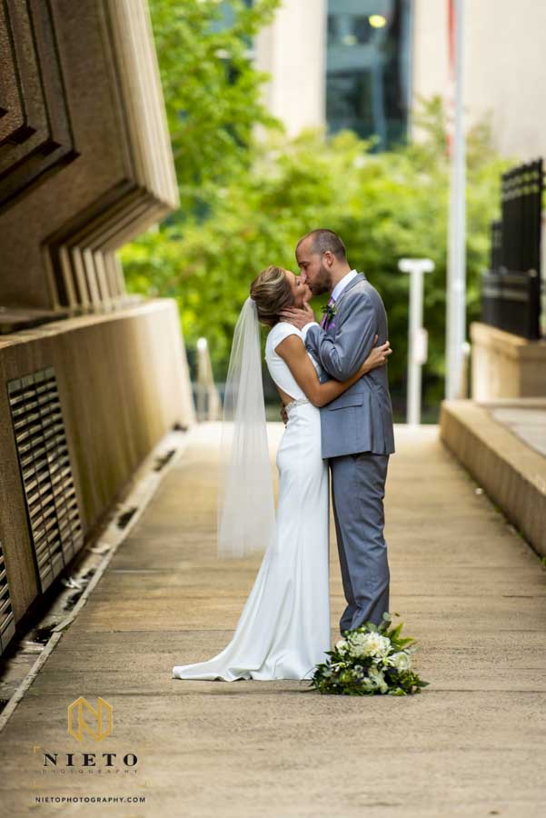 bride and groom kissing each other in an alley in downtown Raleigh