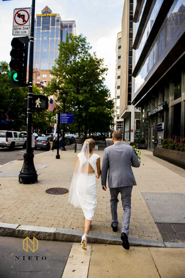 bride and groom crossing the road together after their wedding ceremony
