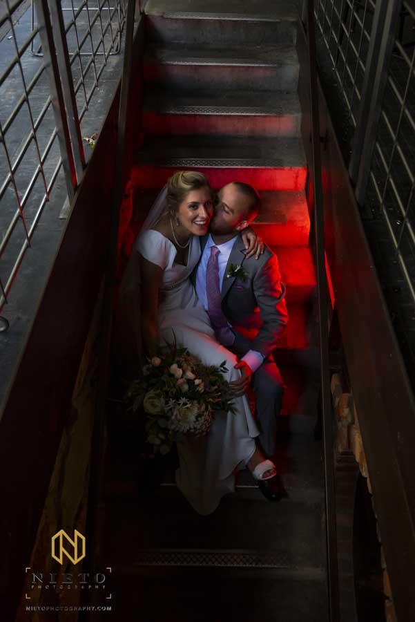 bride and groom sitting on stairs with the groom kissing the bride on the cheek