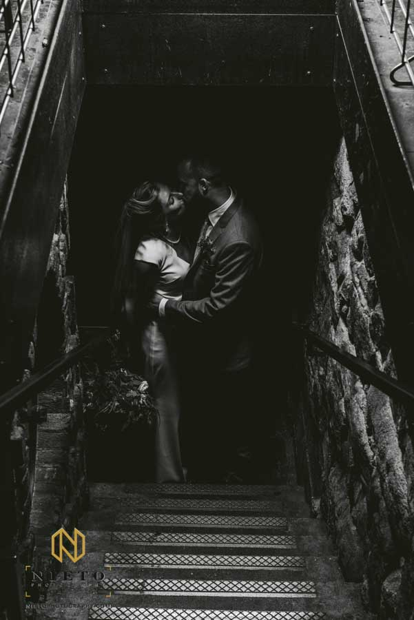 bride and groom kissing at the bottom of a stairwell
