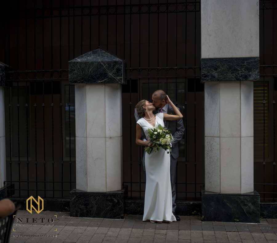 bride and groom kissing while standing against a metal fence