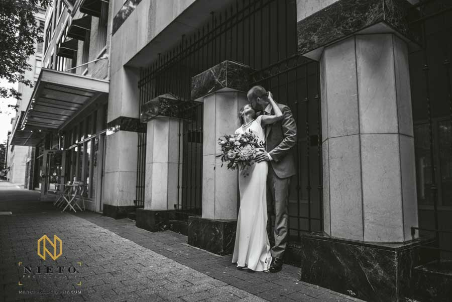 black and white image of a groom and bride kissing on a side walk