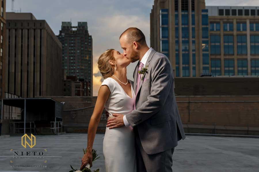 bride and groom kissing on a parking deck at sunset