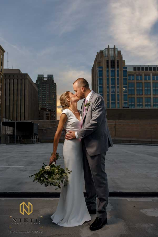 bride and groom kissing on a parking deck with a blue sky behind them