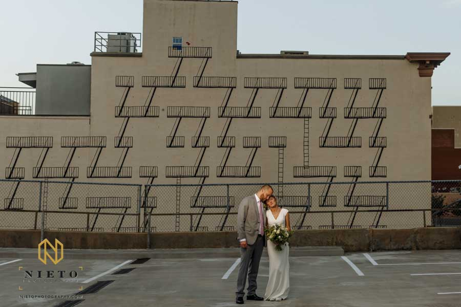 bride and groom leaning into each other as the pose for a portrait on a downtown Raleigh parking deck