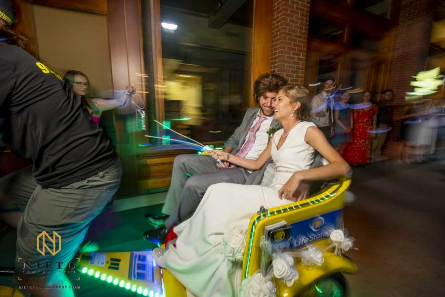 bride and groom riding away on a rickshaw from their stockroom wedding