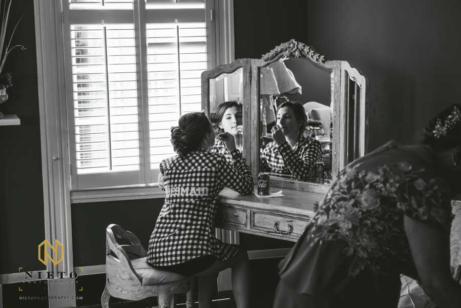 black and white picture of the daughter of the groom eating and looking at her self in the mirror