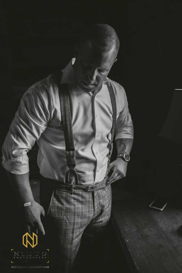 black and white image of the groom getting dressed at the Sutherland