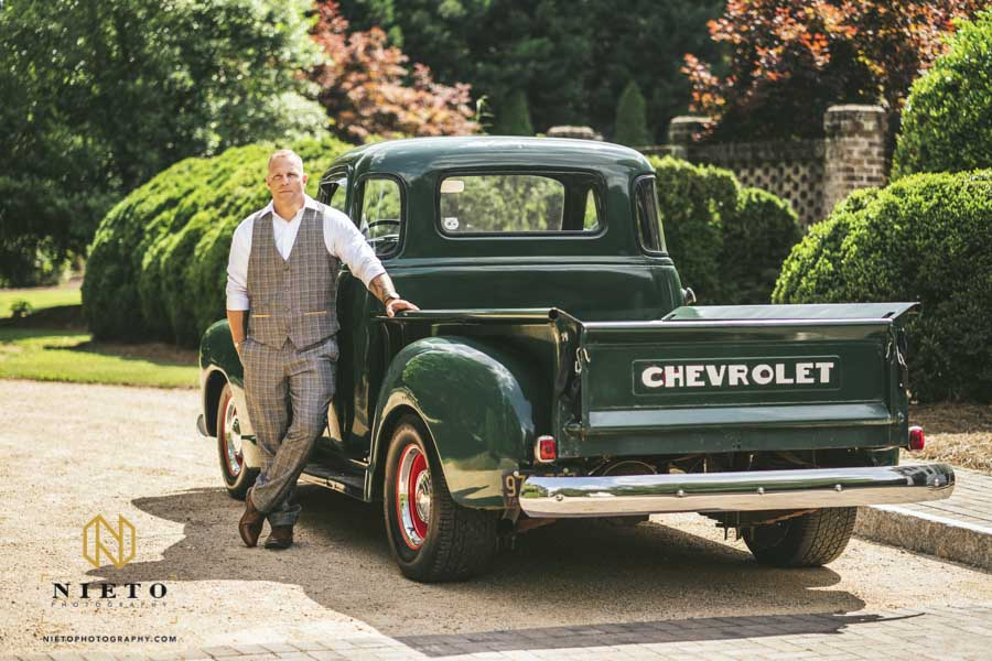 groom posing with a green Chevy truck outside the Sutherland