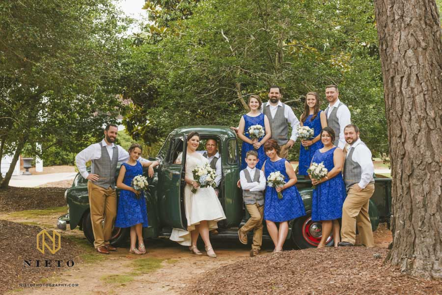 group shot of the wedding party outside of the Sutherland with a green Chevy truck