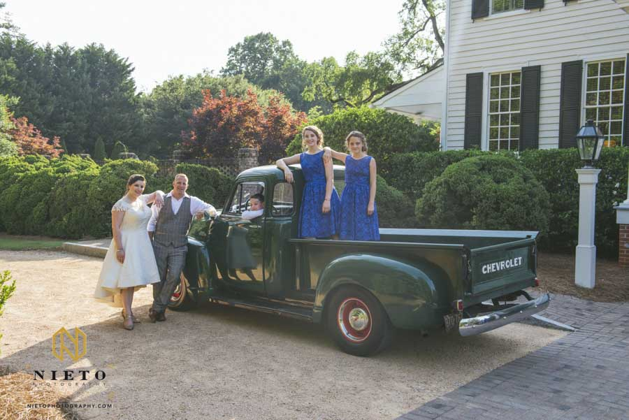 bride and groom with their children posing with a green Chevy truck out side of the Sutherland
