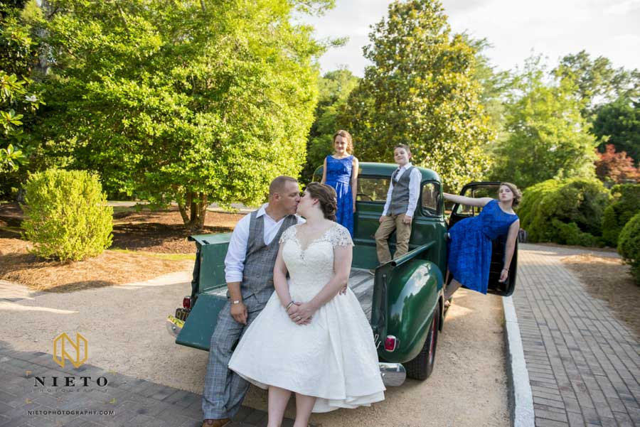bride and groom kissing while they are sitting in the back of a Chevy truck and their kids are behind them