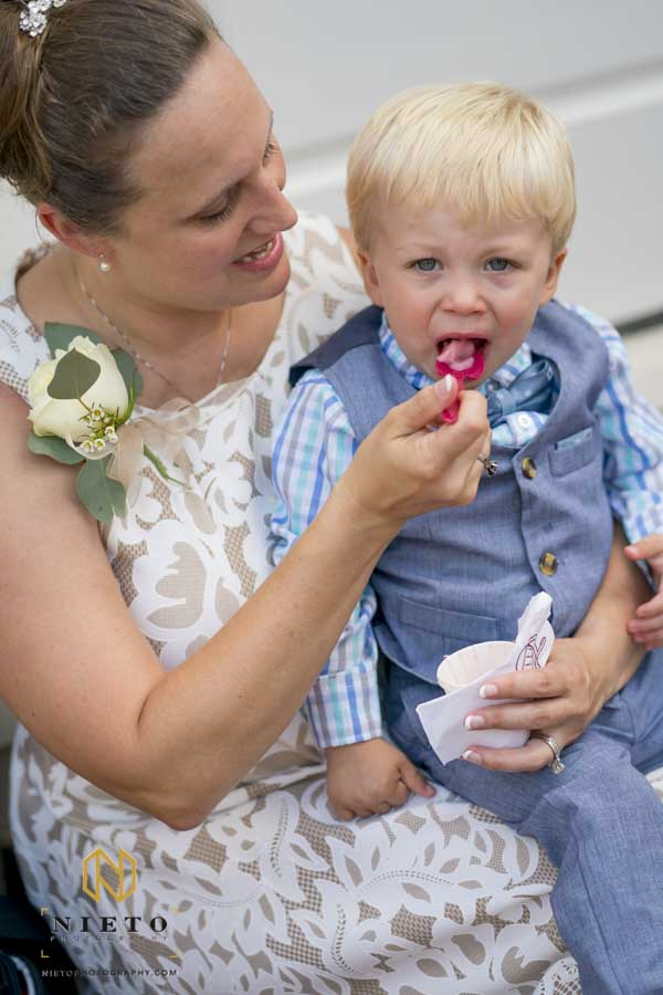 ring bearer being fed Italian ice by his mother