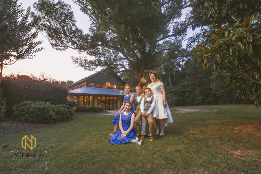 the bride, groom, and their children posing for a portrait outside of the pavilion at the Sutherland