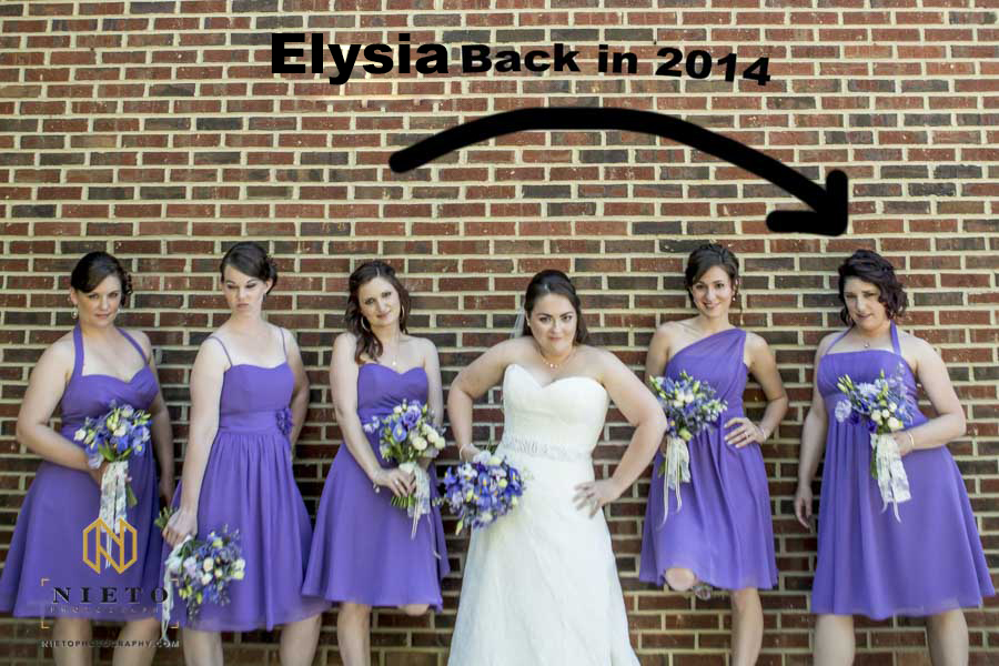 bride and bridesmaids standing up a against a brick wall with writing pointing to one of the bridesmaids