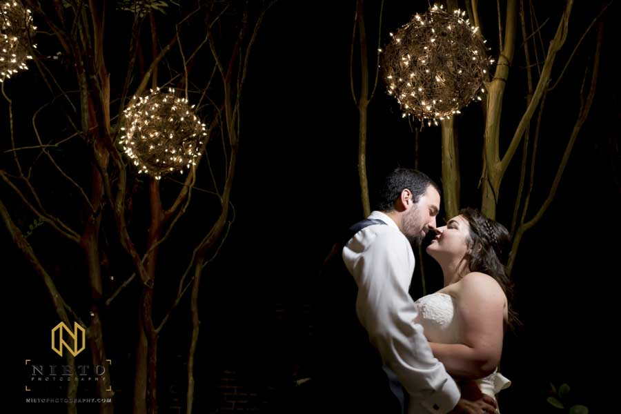 A bride and groom kissing under a lit grape vine ball at the Garden on Millbrook at night